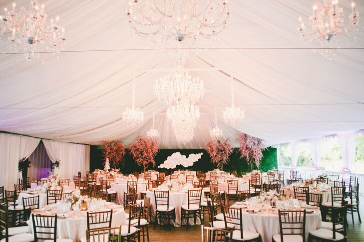 Kat Keane Weddings and Events decked out the reception tent in romantic details—from the cherry blossoms with petals scattered around the ground, to white-covered dining tables decorated with pastel flower arrangements.