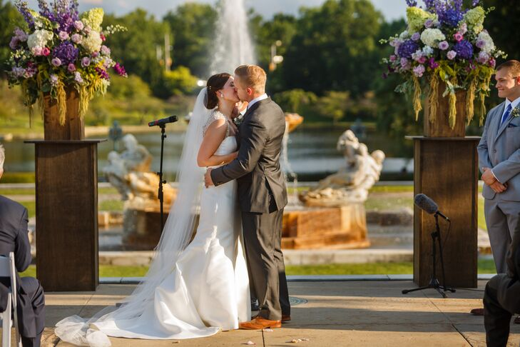 Jackie and Bryan shared their first kiss during the outdoor ceremony, with a beautiful backdrop of the lagoon and fountain on the property. Jackie's elegant silk wedding dress had a long train that trailed in the back, with her cathedral-length veil that blended in beautifully.