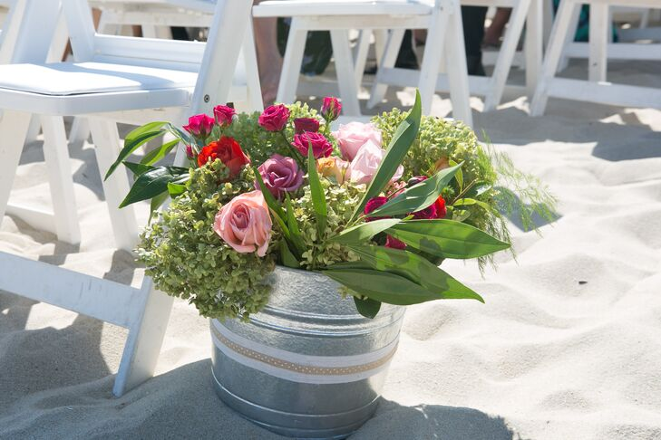 Pink Dahlia Vintage, the couple's florist, put a springlike twist on their beach setting and filled the couple's ceremony with overflowing florals. Each row of white folding chairs was met with a lush arrangement of greenery surrounding bright pink, purple and red roses.