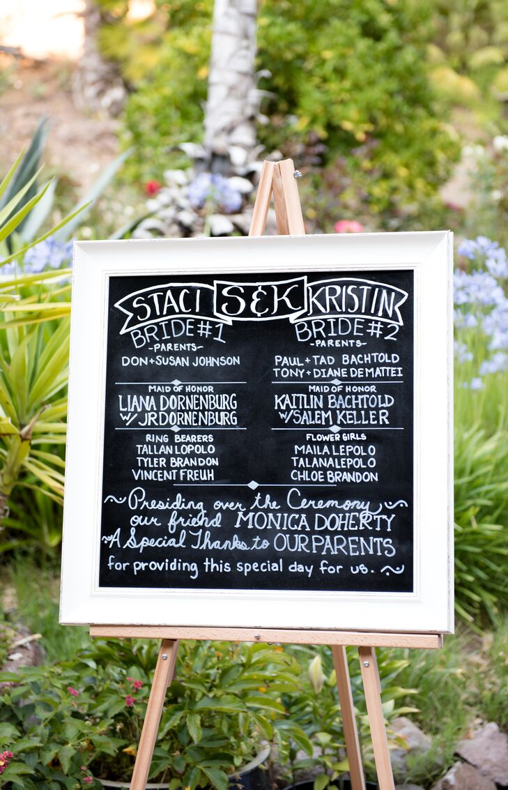 A wood-framed chalkboard outlined the details of the ceremony, including the names of the brides' attendants.