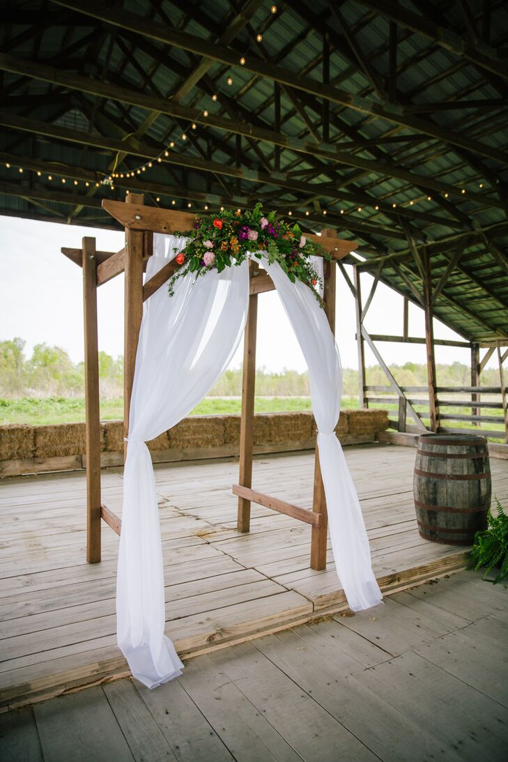 Nicole and Coleman built a DIY wooden wedding arch. They draped it with white linens and had their florist add ferns and fresh, colorful flowers to complete the rustic-chic aesthetic.