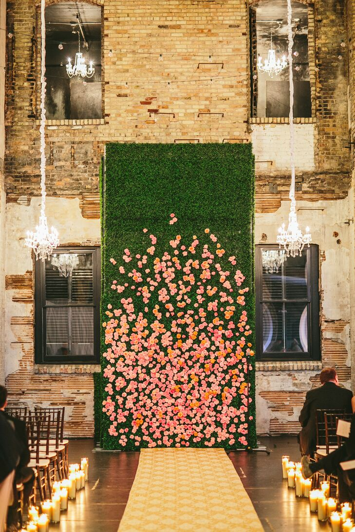 "The newlyweds exchanged vows in front of a green and peach flower wall made with peonies, ranunculus, roses and carnations. ""It was the main thing I was most excited for,"" the bride says. Post-ceremony, the wall was split in half and moved behind the head table and bar area."
