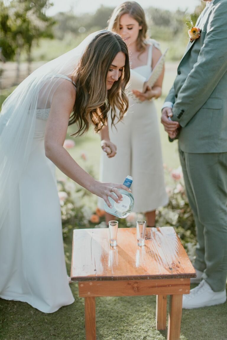 Bride pouring tequila shot during ceremony