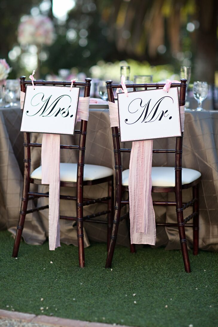 Cute Mr. and Mrs. signs hung from the back of the couple's chairs during the reception.