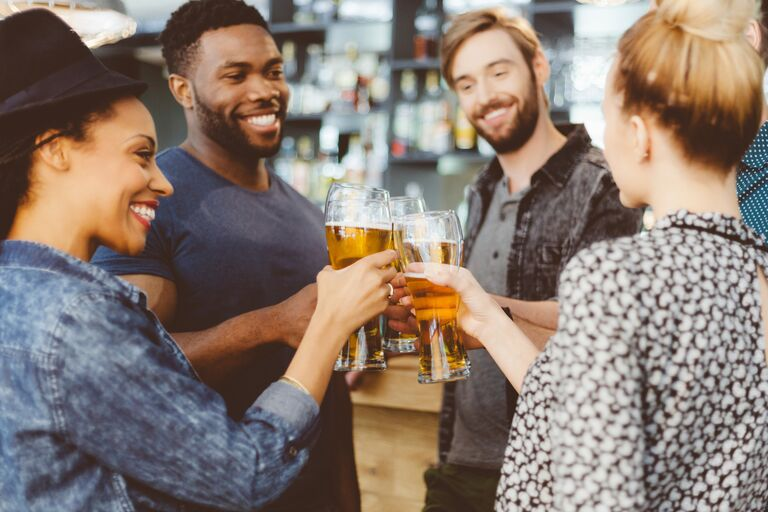 group of people toasting with beer