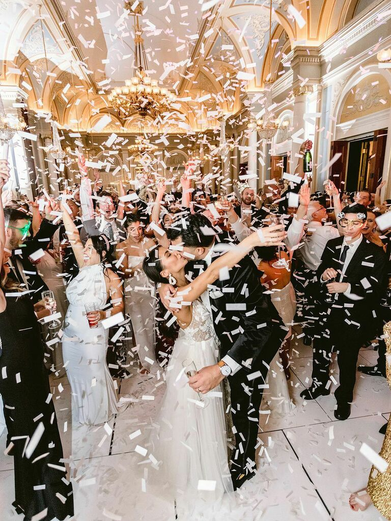 Bride and groom with guests under confetti shower at wedding reception