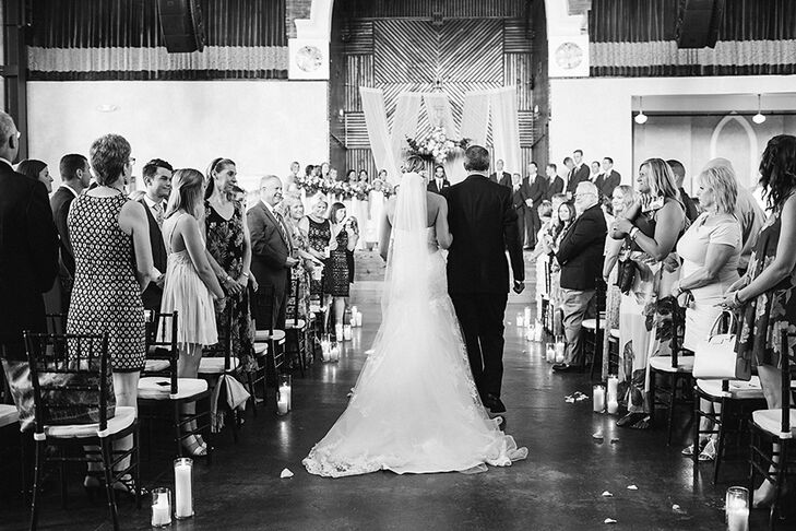 Candles of various sizes were placed at the end of each row to line the aisle during the ceremony. The couple had a 15-foot cross built for the stage and hung fresh flowers and draping greenery from it to complete the romantic look.
