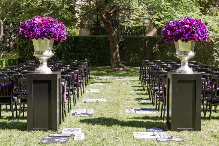 A string quartet played classic rock as guests took their seats in black Versailles chairs placed with violet pillows. The aisle was embellished with various damask patterned stepping-stones, which led to a jacaranda tree hung with black chandeliers.