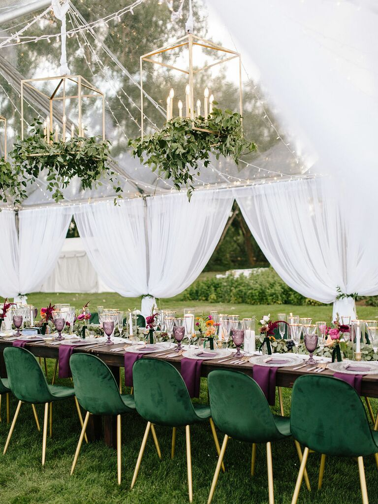 Gold chandeliers with candles inside raised above reception tables at tented wedding
