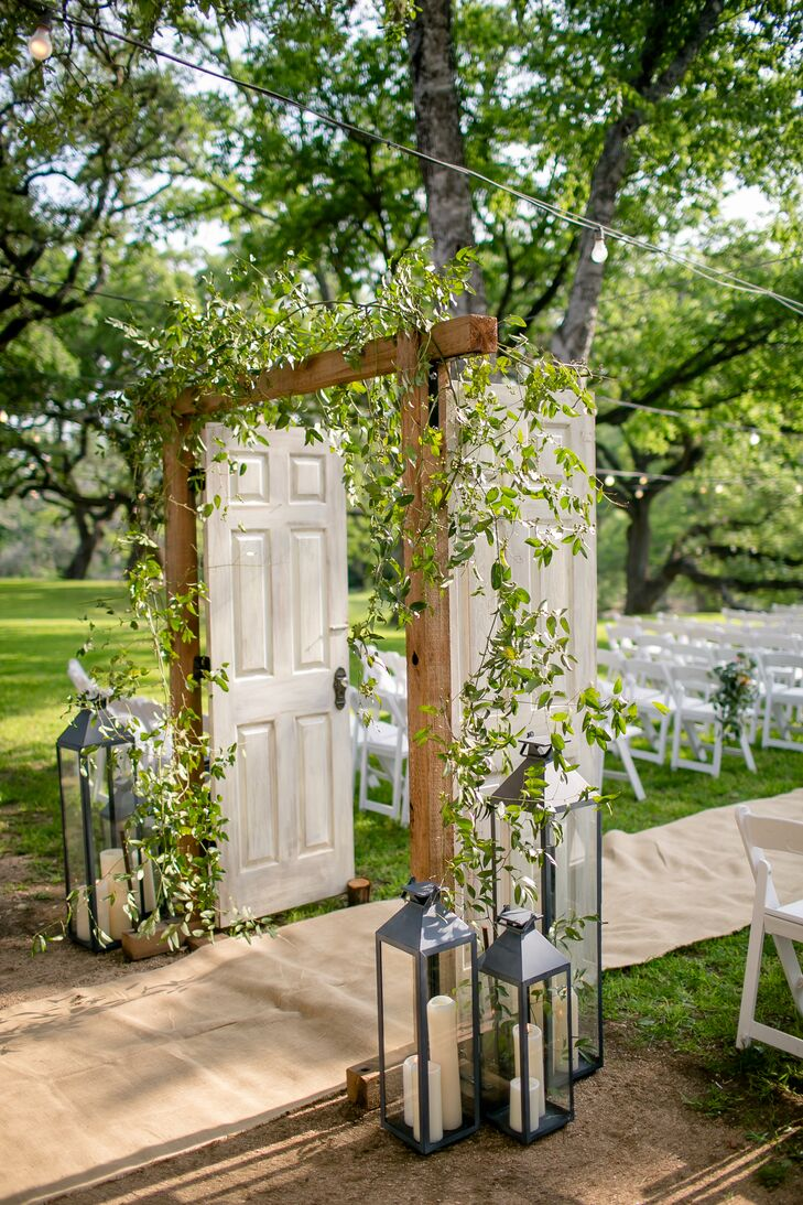 Wooden doors were placed at the top of the aisle, decorated with wild smilax and lanterns for a romantic yet rustic look.