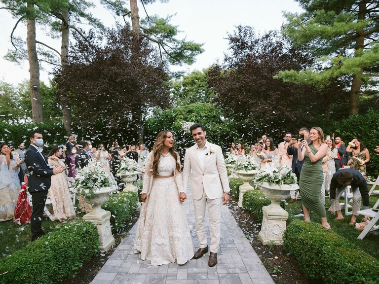 Bride and groom in corresponding ivory outfits for outdoor summer wedding