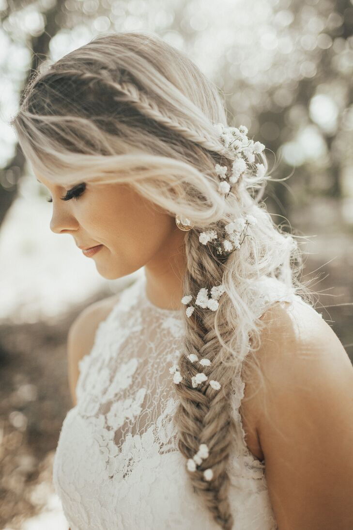 "Jordyn's slightly undone side braid was interspersed with tiny white blossoms, a look that mirrored her bohemian style for the day. ""I chose a white lace BHLDN, form fitting, high-neck gown the whole ceremony and reception,"" Jordyn says. ""Very romantic and ethereal."""