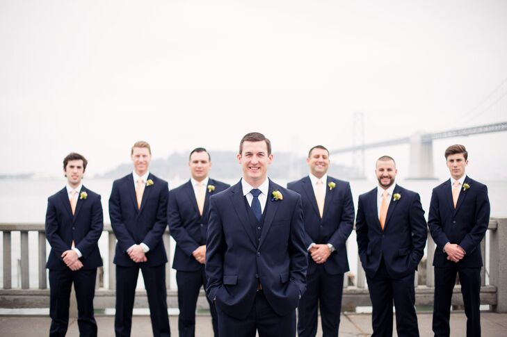 Ryan stood in front of his groomsmen, who all wore matching navy blue suits. Ryan wore a navy paisley-patterned tie, while his groomsmen wore peach ties to match the bridesmaids.