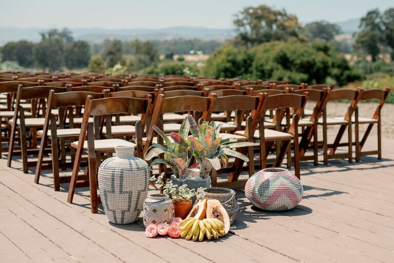 Ceremony aisle decor with woven baskets and fresh fruit