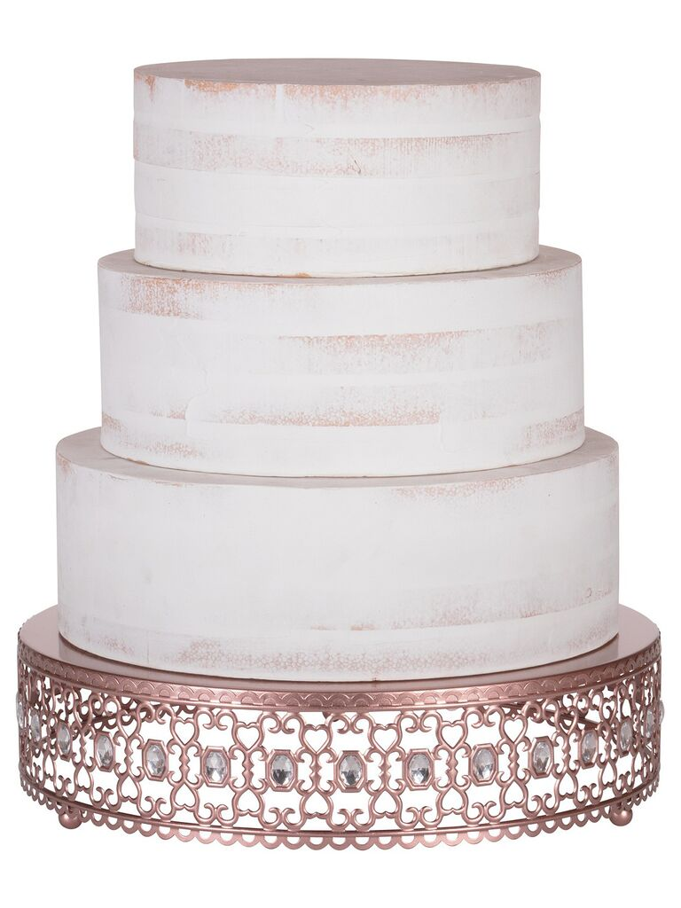 Ornate rose gold and crystal wedding cake stand holding three-tier cake