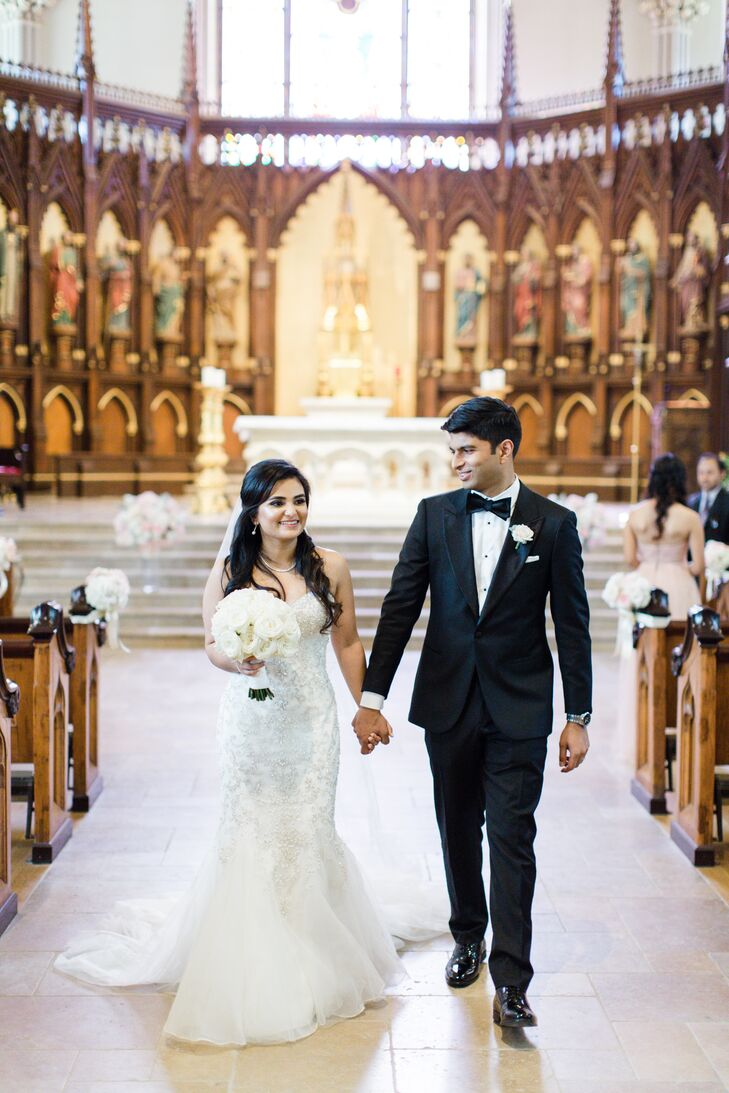 Charlene and Sanket exchange vows in a traditional Catholic ceremony at Old St. Patrick's Cathedral in New York, New York. For decor, the pair let the church's architecture take center stage, adding only understated bundles of white and blush flowers to the end of alternating aisles.