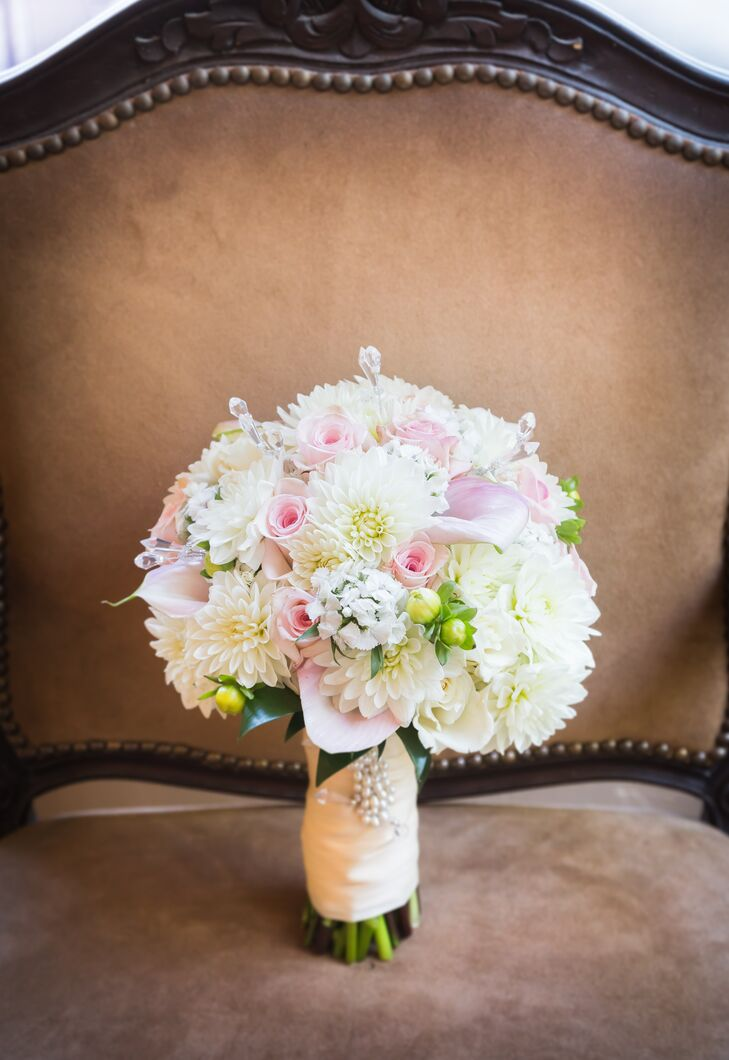 Marisa held a pastel-colored bouquet on the day of the wedding, which was filled with a combination of chrysanthemums, roses and calla lilies. The flowers were held together by a wrap accented with a white beaded pin.