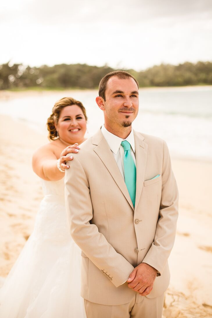 Tim faced one direction as Veronica walked up behind him near the beach waterfront, ready for their first look. Tim wore a light tan suit with a teal tie and pocket square on the wedding day.