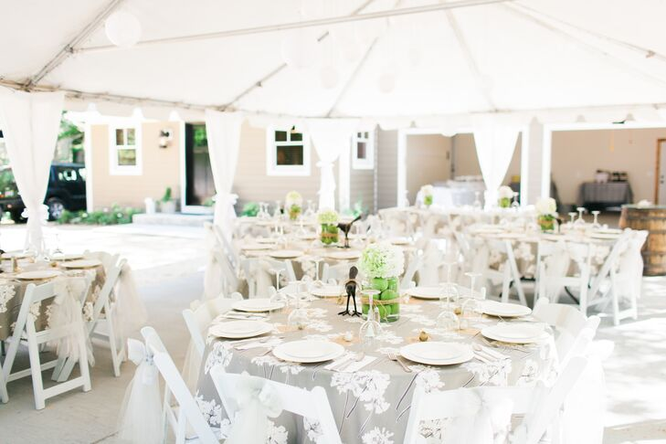 Gray linens covered in a white floral pattern covered the round dining tables. The centerpieces continued the bird motif with metal birds beside the hydrangea and apple arrangements, and a miniature bird figurine at each place setting.
