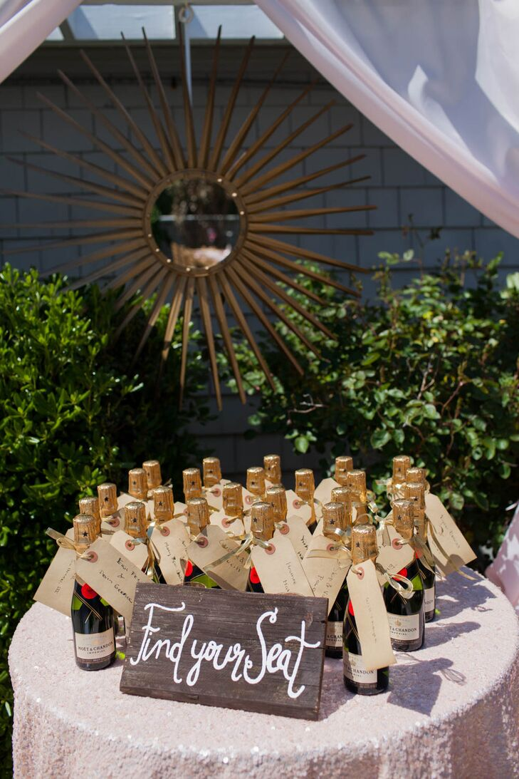 Instead of traditional escort cards, Ryan and Brian got the party started with Moet & Chandon champagne. They wrapped each bottle with a brown-paper tag tied with a gold ribbon. The couple handwrote each guest's name and table on the paper.