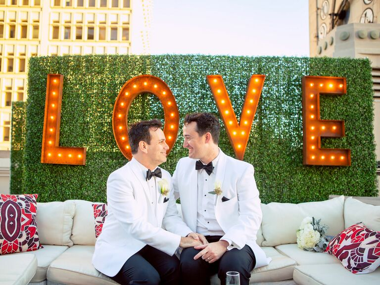 same sex couple wearing white dinner jackets at rooftop wedding ceremony