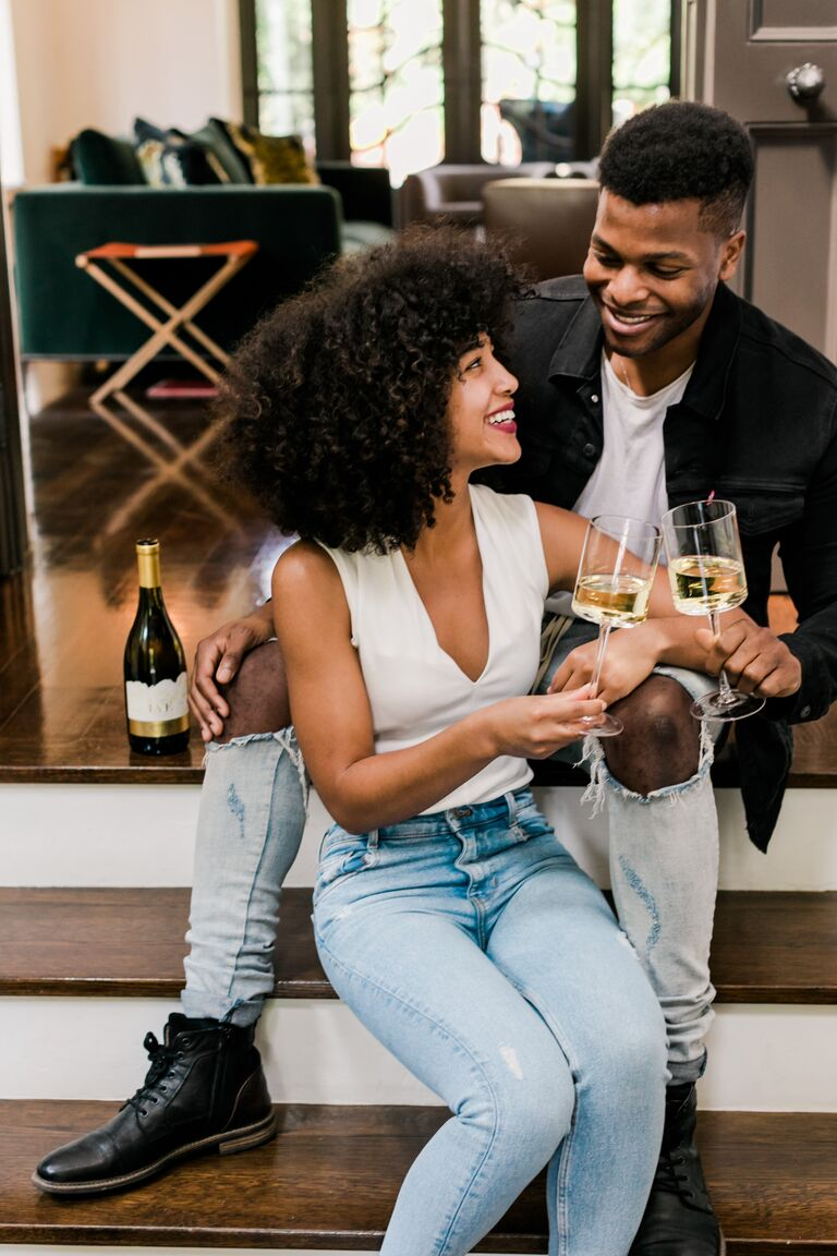 At-home engagement photo with white wine