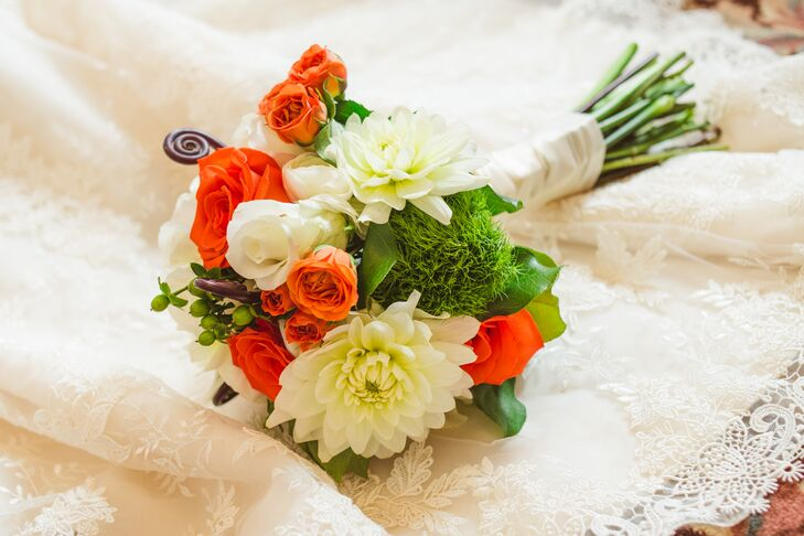 Laura carried orange roses, white dahlias, green trick dianthus and green hypericum berries in her colorful bouquet. She loved that the flowers added a pop of color to the otherwise white winter wedding.