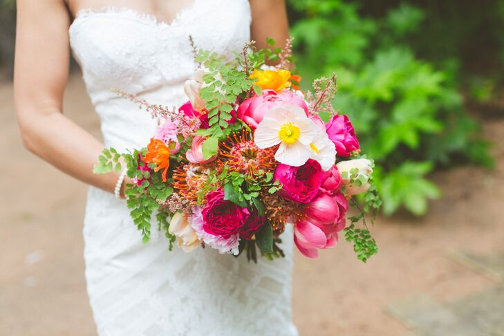 Fresh blooms in bright colors created the modern aesthetic Jill wanted for her bouquet. It had pincushion proteas, peonies, garden roses, ranunculus, parrot tulips, poppies and fern wrapped with gold glitter ribbon.