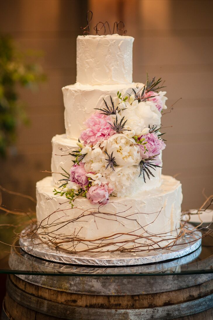 Fresh peonies cascaded down the tiers of the white cake.