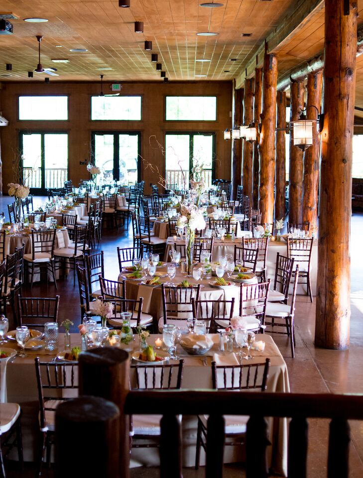 The reception took place inside at Spruce Mountain Ranch in Larkspur, Colorado, where dark-wood dining tables surrounded by matching chiavari chairs filled the space.