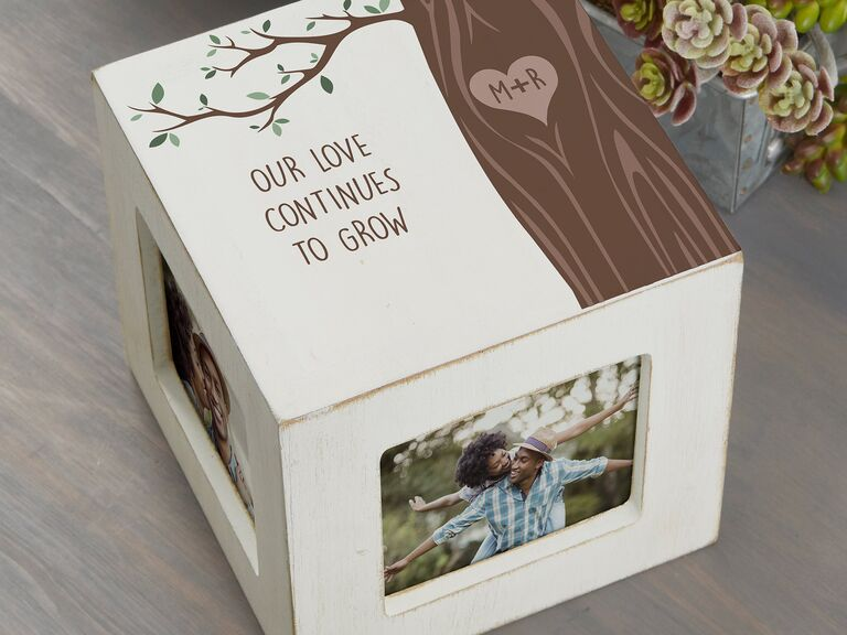Distressed wooden photo block with text reading Our Love Continues to Grow and tree motif