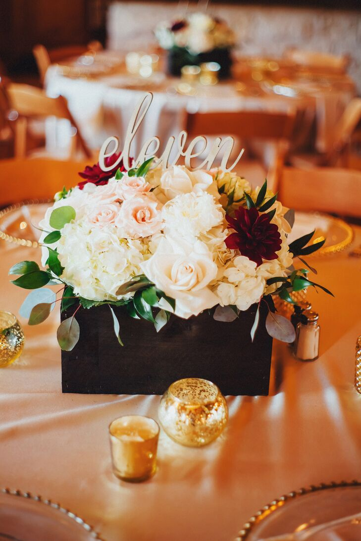 Andrew built and stained DIY wooden flower boxes, which sat on champagne linens. The floral centerpieces contained champagne and blush spray roses with ivory hydrangeas and maroon dahlias and peonies. Script table numbers and gold glass votive candles added an elegant touch.