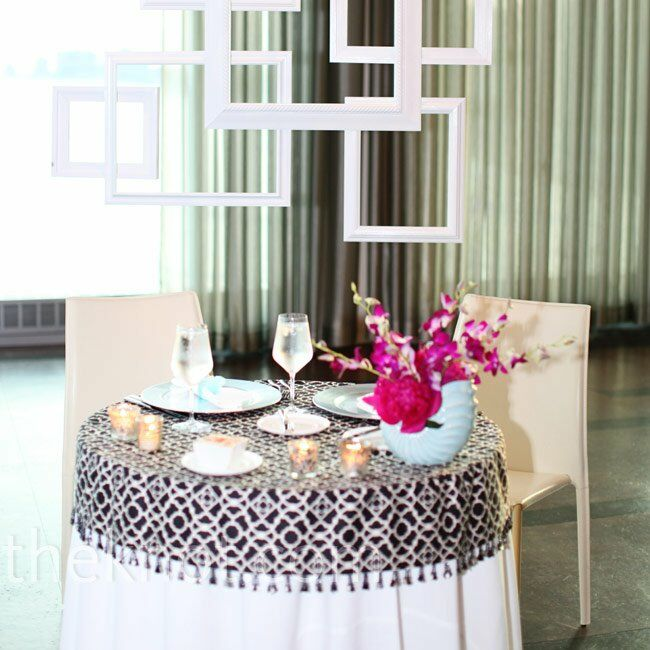 A frame collage created a unique backdrop for the sweetheart table, while a small crystal chandelier hung from above.