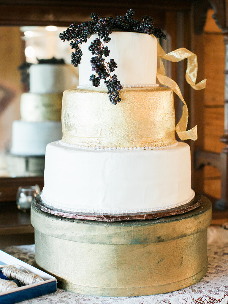 Three tier wedding cake with a black berry accent and gold buttercream