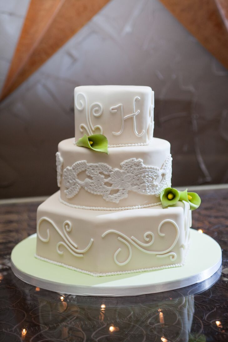 "The wedding cake and groom's cake were made by Whisk Until Sweet, a family friend of the couple's. ""They turned out simply delicious,"" Rebecca says. The wedding cake featured three ivory tiers, with a center tier covered in a white lace pattern with fondant green calla lilies."