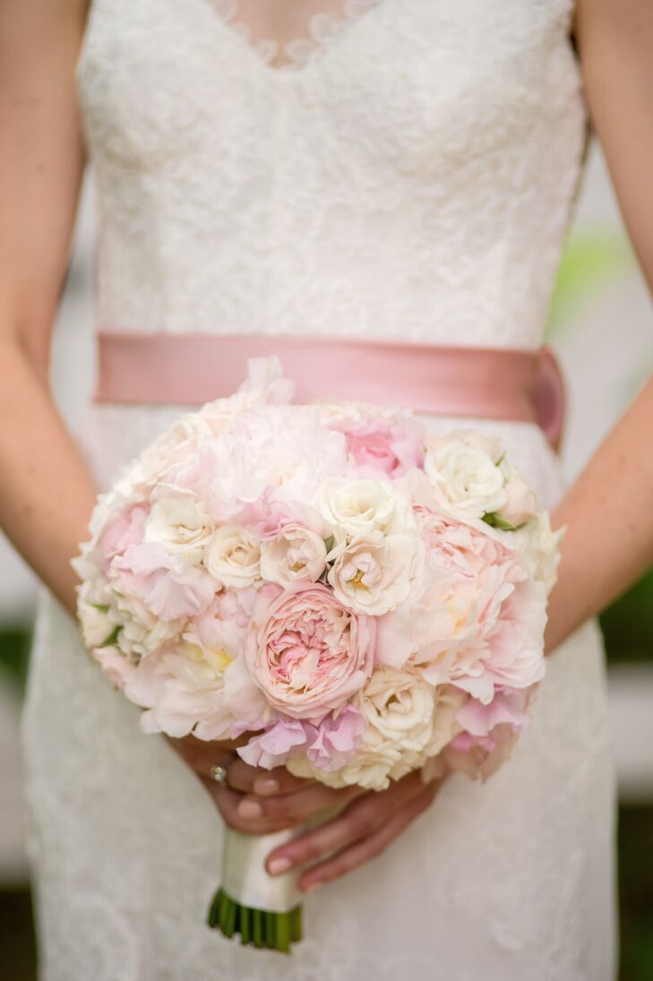 Inspired by her  grandmother's garden, Nellie chose peonies for the day's main flower. She carried a classic bouquet of f white and pink peonies with coral garden roses and ranunculus, tied with an ivory satin ribbon and pearl pins.