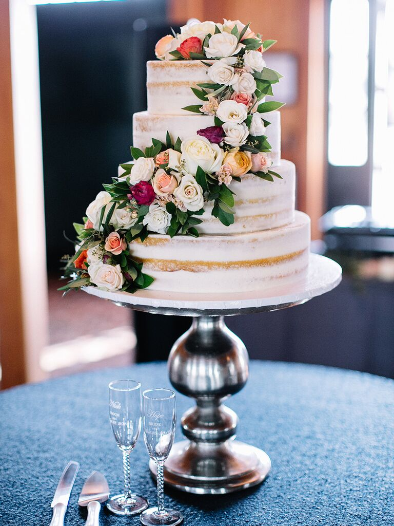 Small nearly naked wedding cake with a spray rose cascade