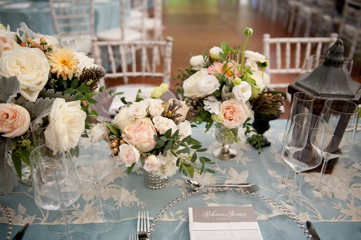 To introduce an element of texture and depth to the reception decor, while playing up the wedding's garden inspiration, Dragonfly Events created several centerpiece styles for the reception tables. Round tables boasted candle-centric centerpieces or large footed-bowl arrangements filled with hydrangeas, dahlias, roses, sage green foliage and succulents, while the long farm tables featured a series of glass vases filled with fall sedum, ranunculus, garden roses and dahlias, interspersed with lanterns and mercury glass candleholders.