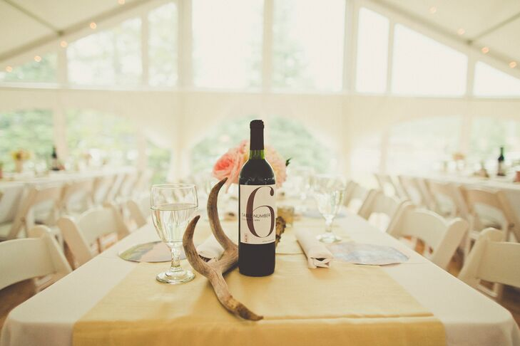 """Each table had white and light pink flower arrangements in white vases complemented by deer antlers which my dad has collected over the years, and the table numbers were printed on wine labels which were put on to red wine which my husband made over our engagement,"" Gracie says."
