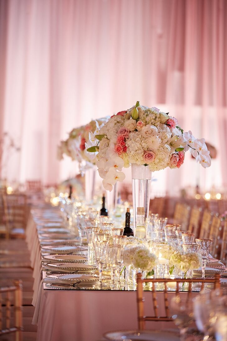 "Maria and Chris decorated the four imperial head tables with table mirror toppers and three-foot towering rose, hydrangea and orchid centerpieces. ""I wanted a classic, elegant look that was still dramatic,"" Maria says."