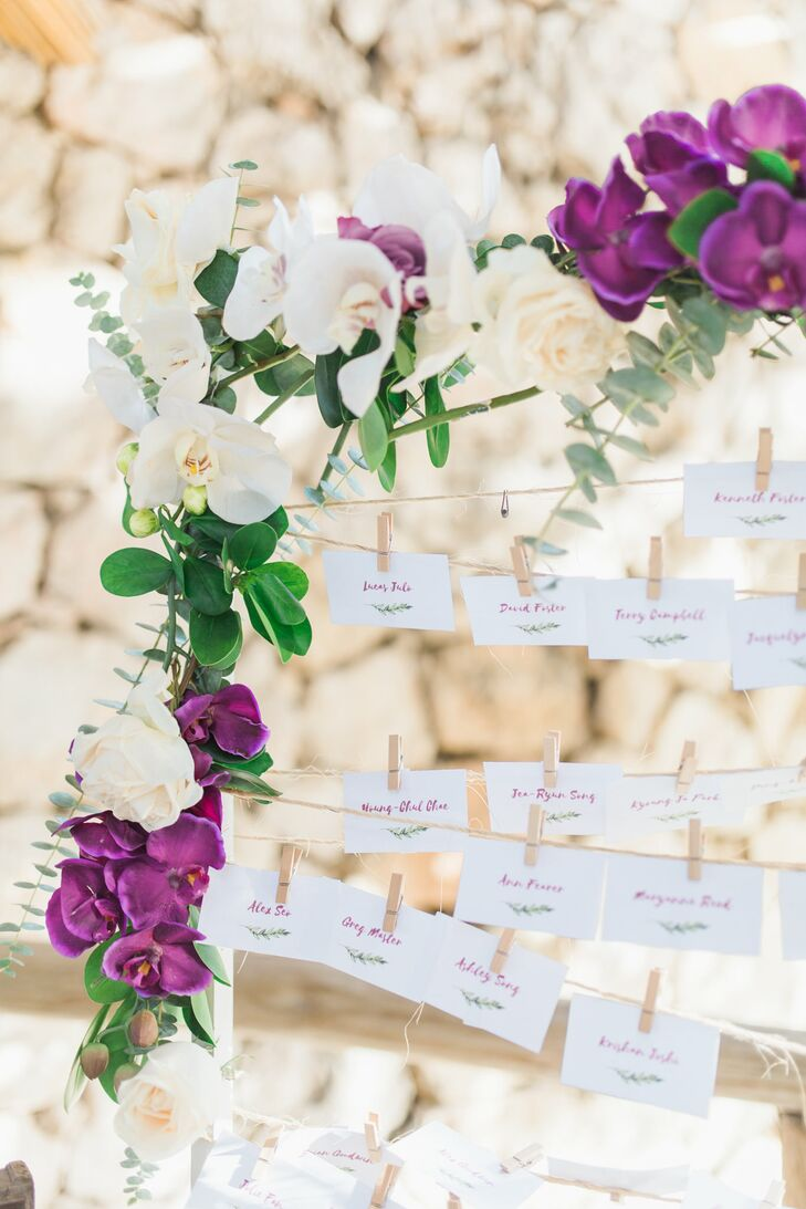 The names of the couple's family members and friends were hand-lettered in purple ink on classic white cards, pointing guests in the direction of their seats. The cards featured natural flourishes and were displayed on twine framed by eucalyptus and orchids.