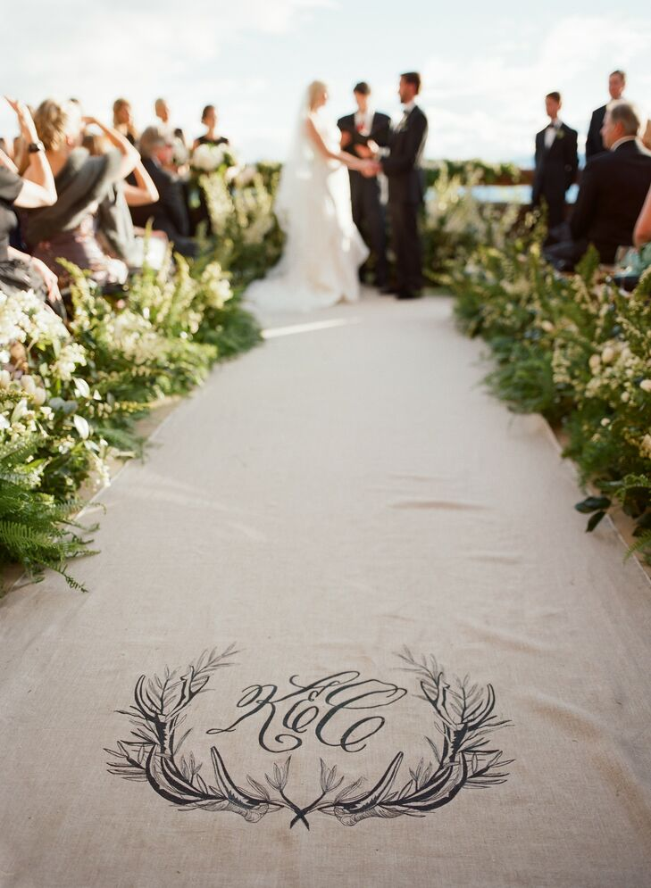 The aisle runner was a natural linen with the couple's wedding logo of interweaving branches embroidered into it. The aisle was lined with tall greenery that came into a U around the ceremony site, where Katie and Cody exchanged vows in order to keep the view in the background the primary focus.