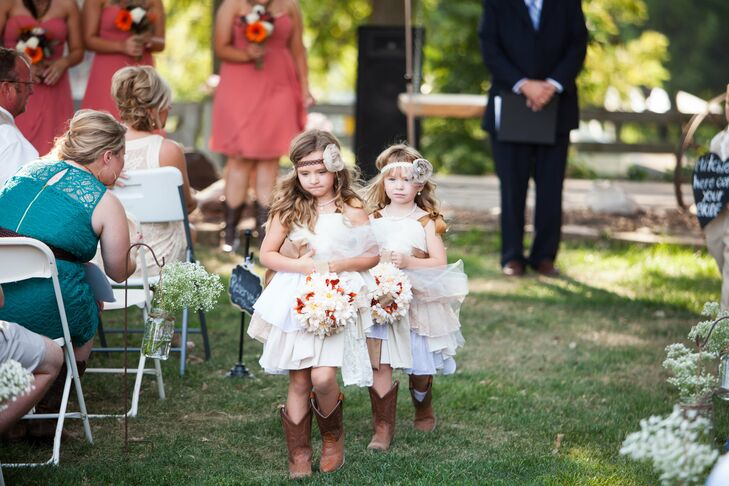 Flower girls dressed in layered white dresses with rosette headpieces carried floral pomanders and accessorized with cowboy boots, like the bridesmaids.