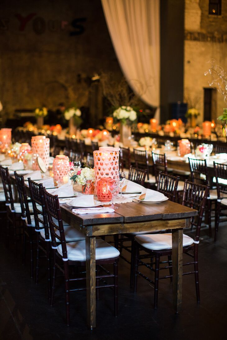 To create a casual feel at the reception, Molly and Boston used long farm tables for their guests. Pink lanterns, which were also used to line the ceremony aisle, decorated the tables along with short flower arrangements and plenty of candles.