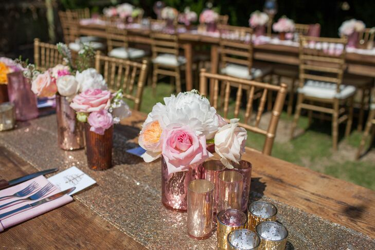 Renee Landry Events arranged white peonies, pink roses and peach garden roses to serve as the centerpieces. Sparkly gold table runners, metallic vases and gold chiavari chairs added plenty of glamour to the wooden farm tables.