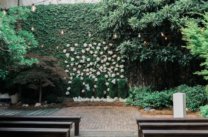 Decor was kept minimal in the naturally beautiful space at The Atrium in Wilmington, North Carolina. A wall of greenery and white roses was the only ceremony decor needed.