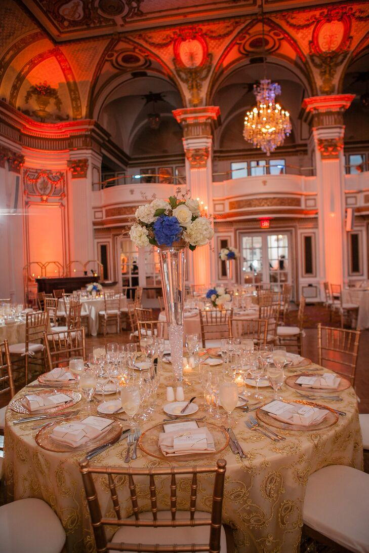The reception saw a mix of high and low floral arrangements, consisting of blue hydrangeas, white roses and sprigs of gold as an accent. The tables matched the baroque gold architecture of Fairmont Copley Plaza in Boston, Massachusetts.