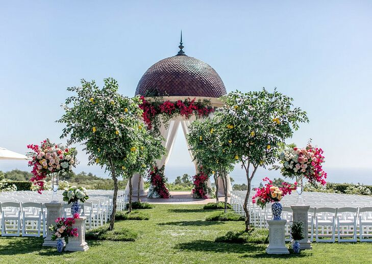 Luxurious Waterfront Ceremony Site with Trees, Colorful Flowers and Folding Chairs