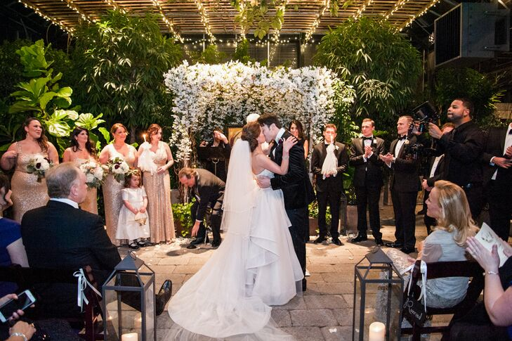 "Planterra Conservatory in West Bloomfield, Michigan, provided the gorgeous arbor of white flowers over the altar. After the kiss, a gospel choir broke into a lively rendition of ""Oh Happy Day."""