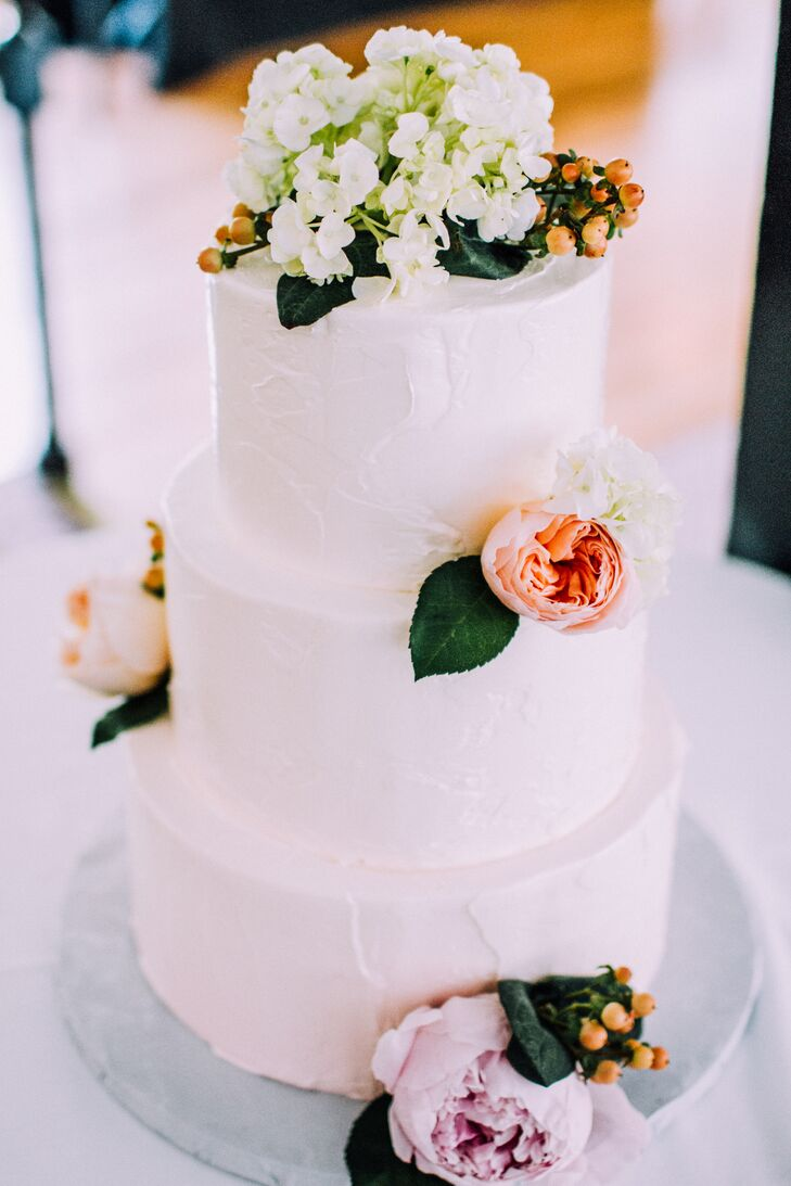 After a brunch-inspired cocktail hour and sit-down dinner, the newlyweds treated their guests to a decadent chocolate chunk and pink champagne cake with strawberry filling. Hippie Chick Bakery gave the three-tier confection a textured, ombre appearance with pink and white buttercream frosting, adding pink and peach cabbage roses to give the cake a romantic edge.